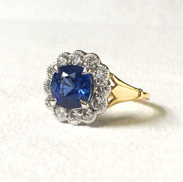 cushion cut blue sapphire with floral inspired diamond halo in yellow gold and platinum