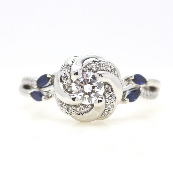 round diamond with pave swirl halo and split shank pave band with accent marquise blue sapphires