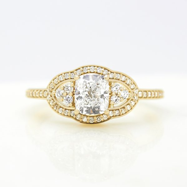 elongated cushion diamond trilogy engagement ring bead set diamond halo and band set in yellow gold