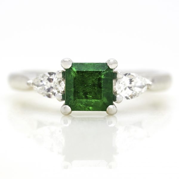 emerald with pear diamond side stone trilogy engagement ring