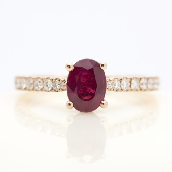 oval ruby engagement ring with pave diamond band in rose gold