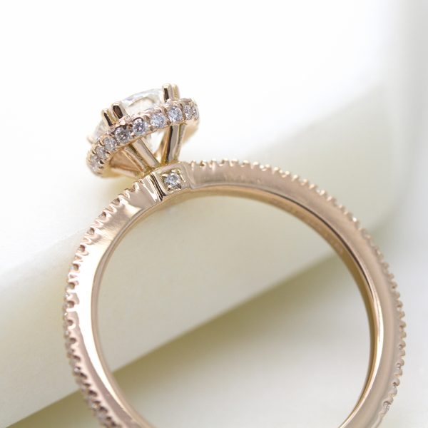 rose gold engagement ring with pave collet detail and pave set diamond on the bridge