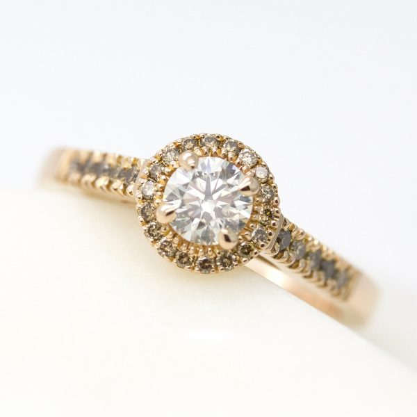 round diamond with cognac diamond halo and pave band set in rose gold