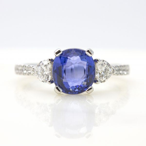 cushion cut blue sapphire with heart diamond accent stones and pave diamond engagement ring