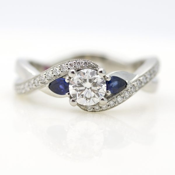round diamond with diamond pave sweeping band and accent pear blue sapphires engagement ring