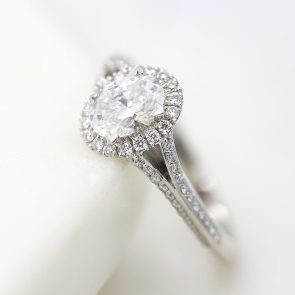 oval diamond engagement ring with diamond halo and diamond pave split shank knife edge band