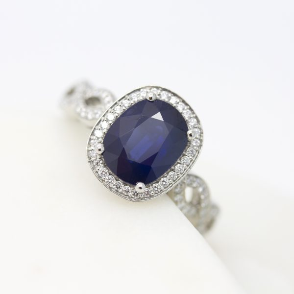 Oval blue sapphire with diamond halo and diamond pavé weaved band engagement ring set in platinum