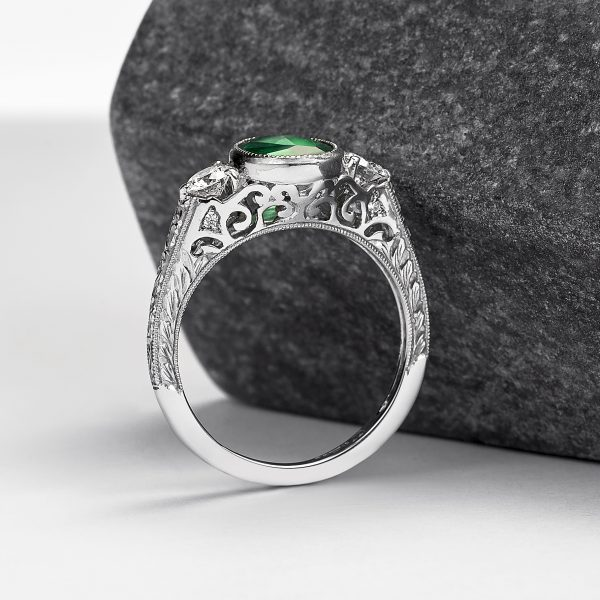 emerald engagement ring with filigree cut outs and hand engraved engagement ring