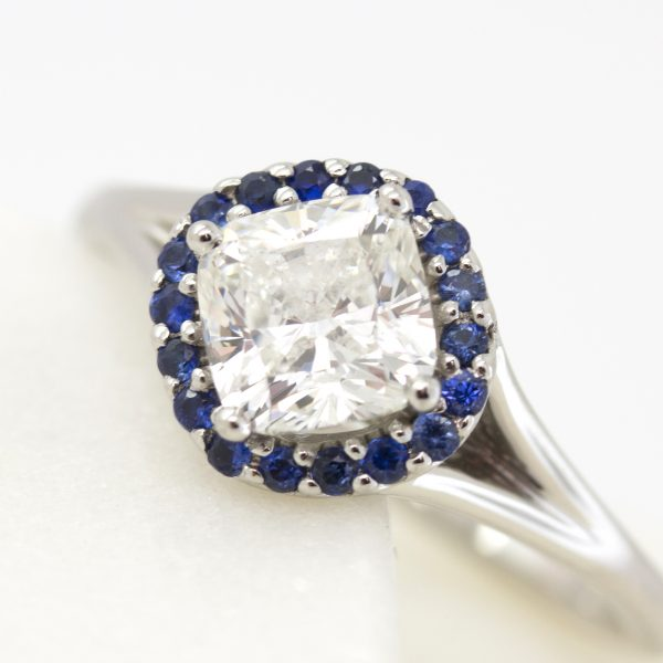 cushion cut center diamond with blue sapphire halo engagement ring set on a bias with split shank