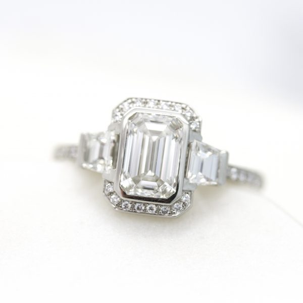 emerald cut diamond with step cut trapezoids in trilogy engagement ring