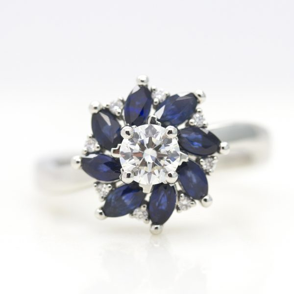 round diamond with marquise cut blue sapphire floral halo