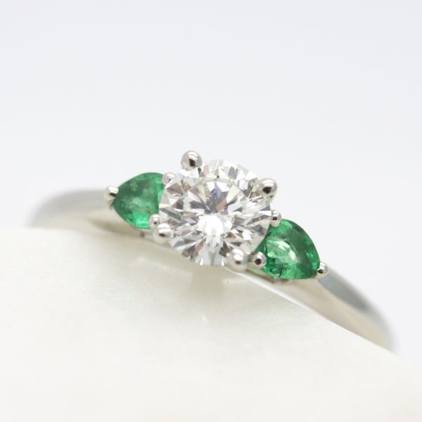 trilogy engagement ring with round diamond centre with emerald pear side stones