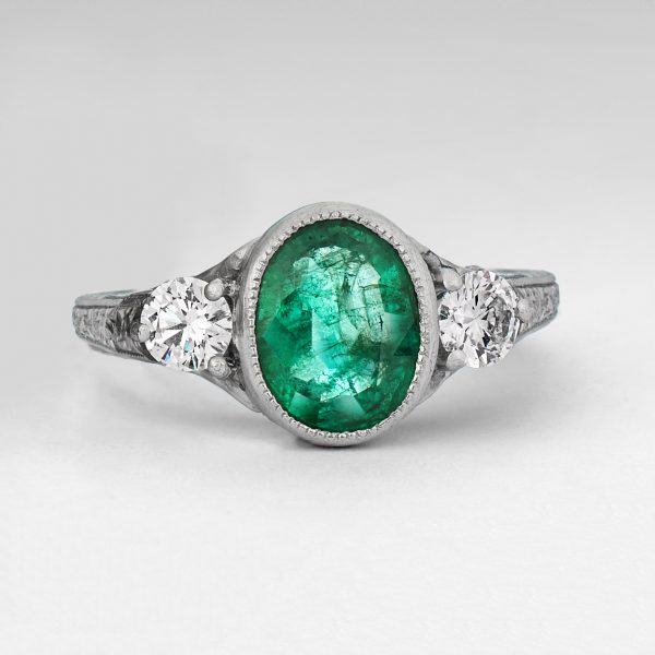 oval emerald with round side diamonds and milgrain engagement ring