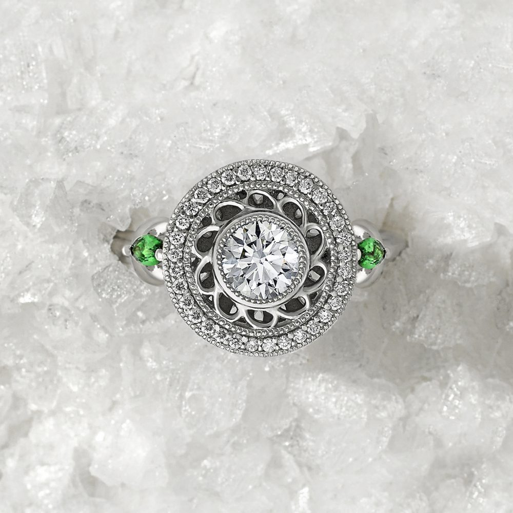 round centre diamond with filigree halo and marquise tsavorites platinum engagement ring