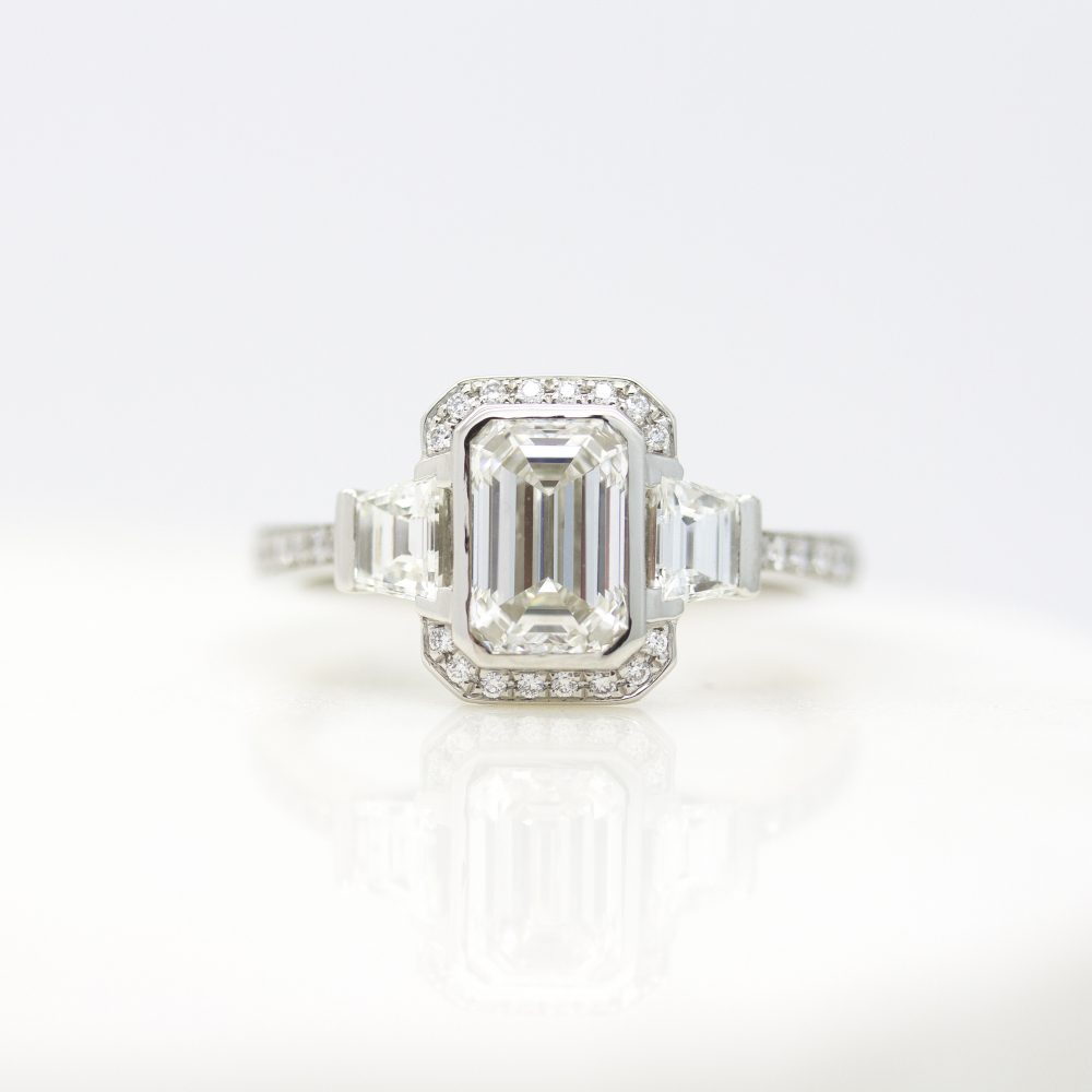 emerald cut diamond with north south halo and accent trapezoids