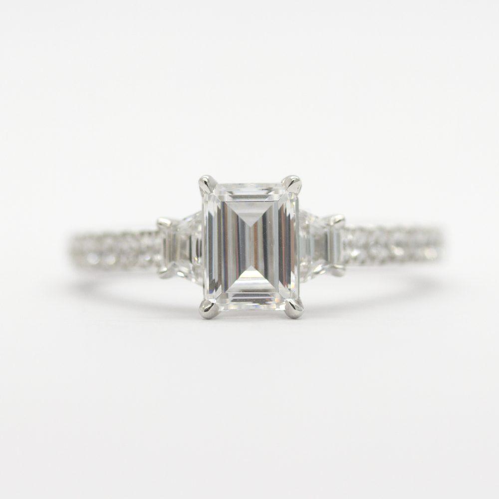Emerald cut diamond with trapezoid diamond side stones