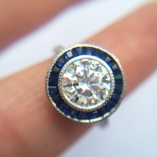 round diamond with blue sapphire custom cut halo and milgrain detail