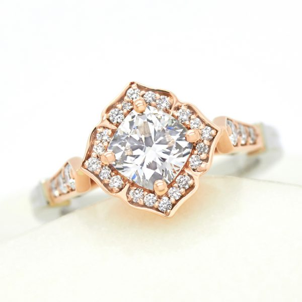 cushion cut diamond set on a bias with vintage inspired bead set halo in rose gold engagement ring