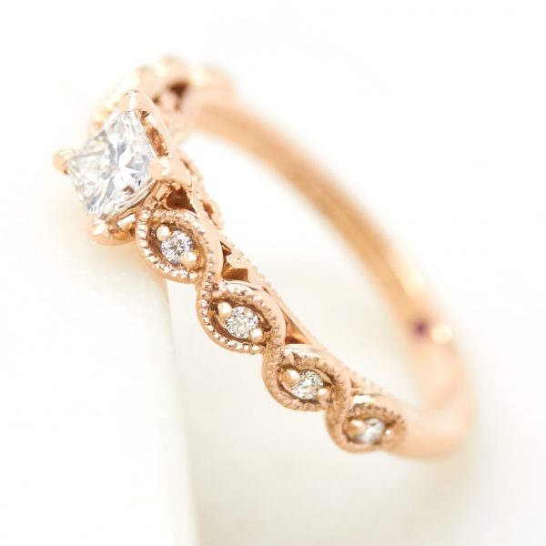 princess cut diamond rose gold engagement ring with twisted milgrain and bead set diamond band