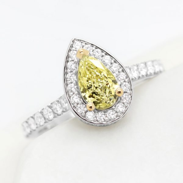 pear yellow diamond with yellow gold claws and platinum diamond halo engagement ring