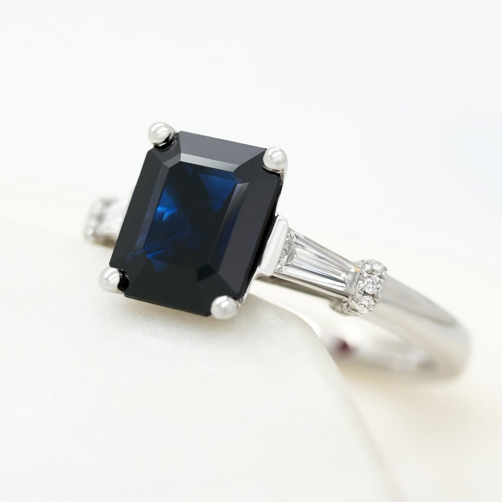 emerald cut blue sapphire trilogy engagement ring with tapered diamond baguettes