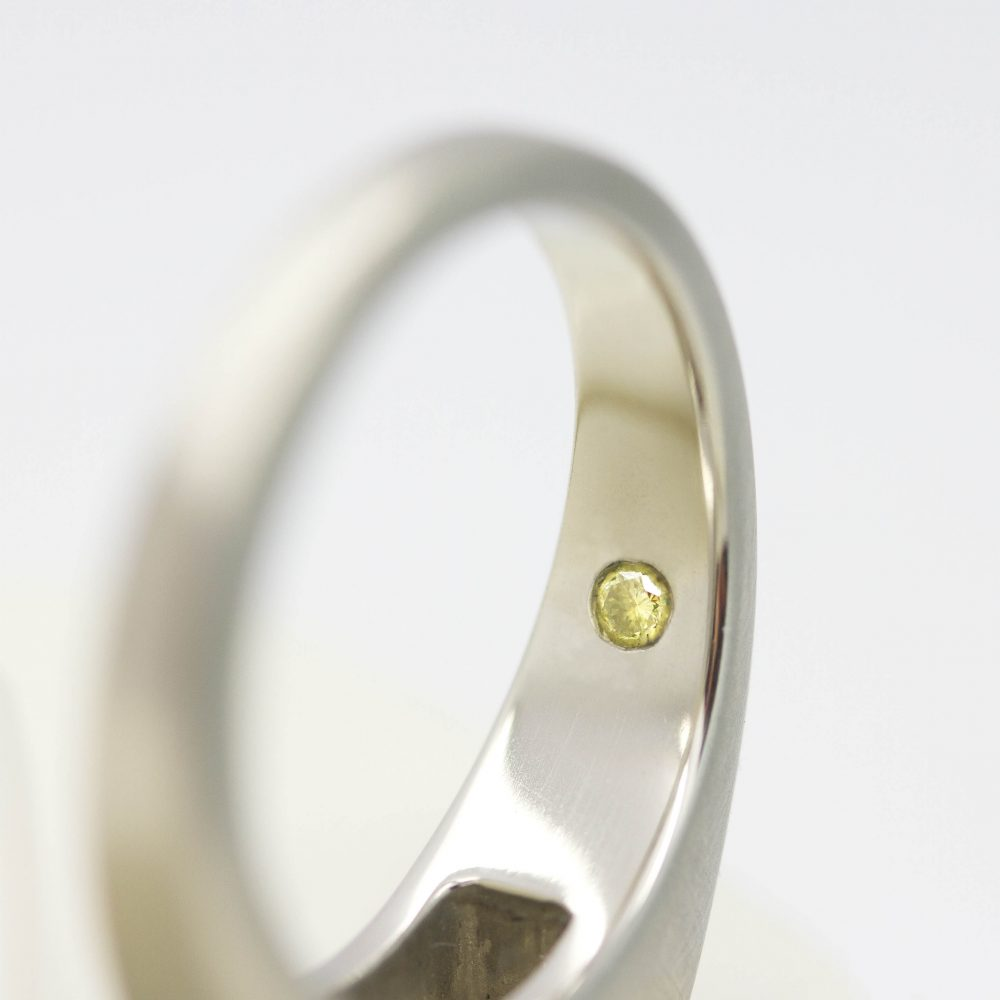 yellow diamond set on the inside of a band signature stone