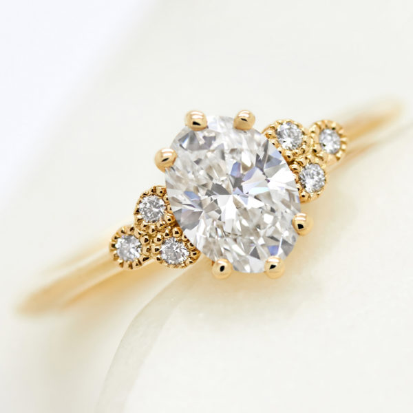 oval diamond with round accent stones with milgrain in yellow gold