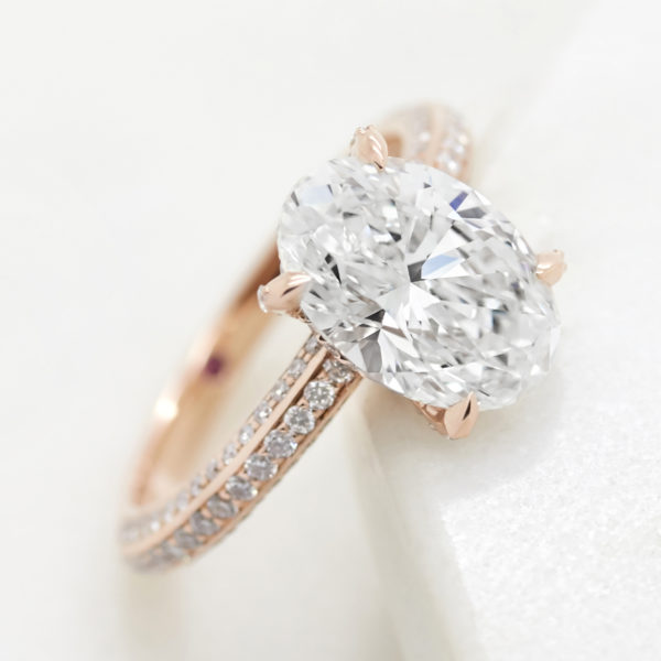 oval diamond with three row diamond pave band in rose gold