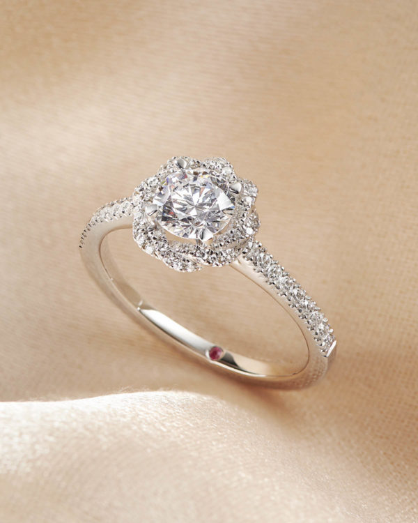 Round diamond center and twisted pavé diamond halo set in platinum engagement ring
