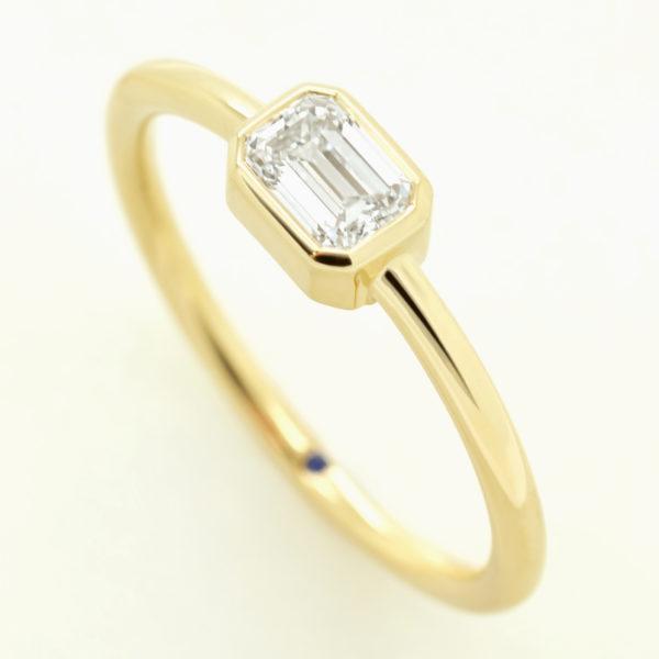emerald diamond bezel set yellow gold