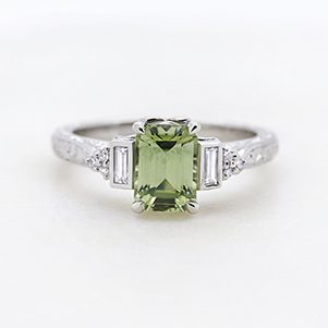 engagement ring with pale green sapphire and emerald side diamonds with milgrain