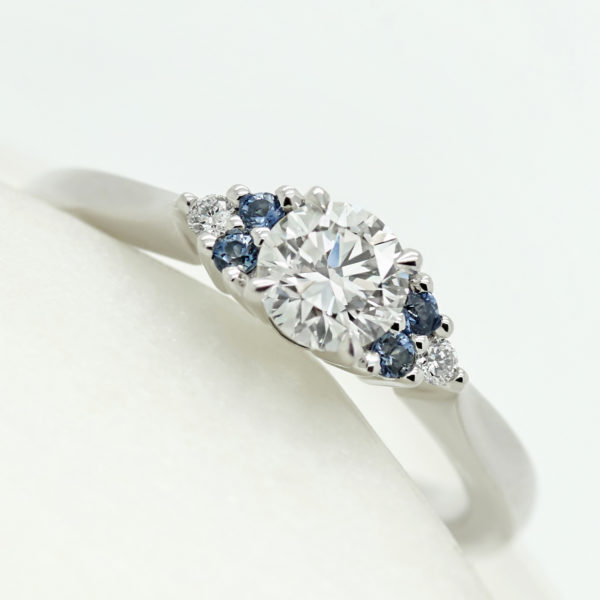 round diamond trilogy engagement ring with accent blue sapphires