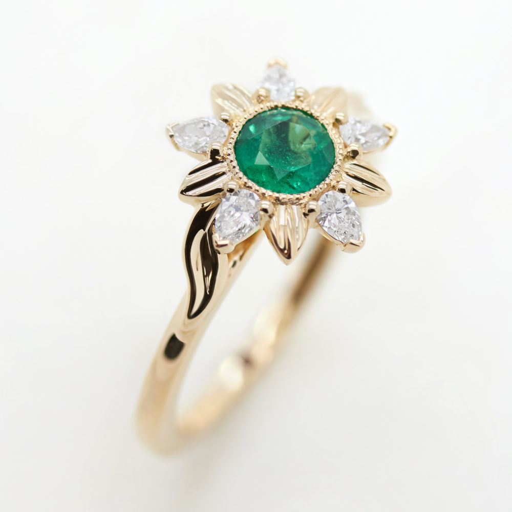 round emerald organic engagement ring with diamond floral halo in yellow gold