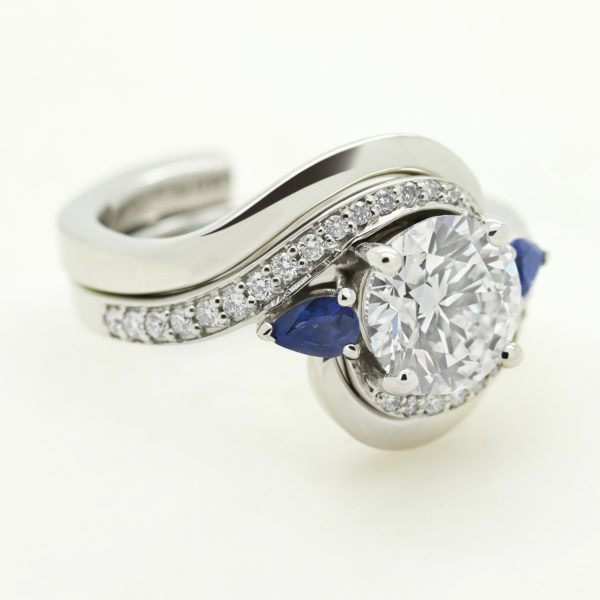 round diamond trilogy engagement ring with pear blue sapphires and sweeping polished fitted matching wedding band