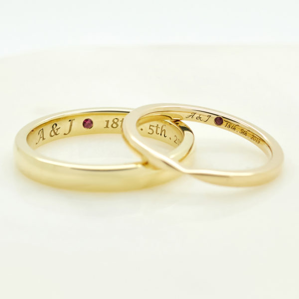 yellow gold matching ladies and mens wedding rings with date inscription engraving and ruby