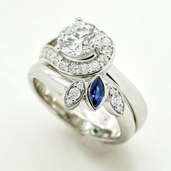 sweeping diamond halo engagement ring with matching blue sapphire and diamond marquise matching wedding ring