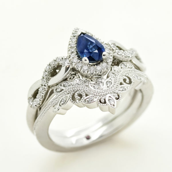 pear blue sapphire engagement ring with matching organic floral wedding ring